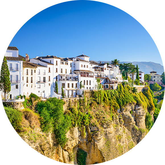 White houses lined up by cliff edge abroad to promote Much Ado About Insurance Brokers - Personal Travel Insurance