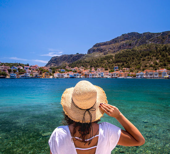 Lady with straw hat gazing into the ocean to promote Much Ado About Insurance Brokers - Personal Travel Insurance