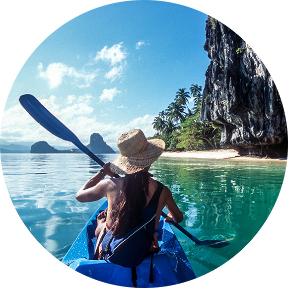 Young girl kayaking through scenic river to promote travel insurance by Much Ado About Insurance